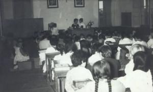 Interior da antiga escola de Burela nunha clase coa mestra e as alumnas.