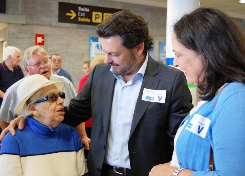 El secretario xeral da Emigración  y la delegada de la Xunta de Galicia e A Coruña, con el participante de más edad (92 años) en el aeropuerto de Alvedro