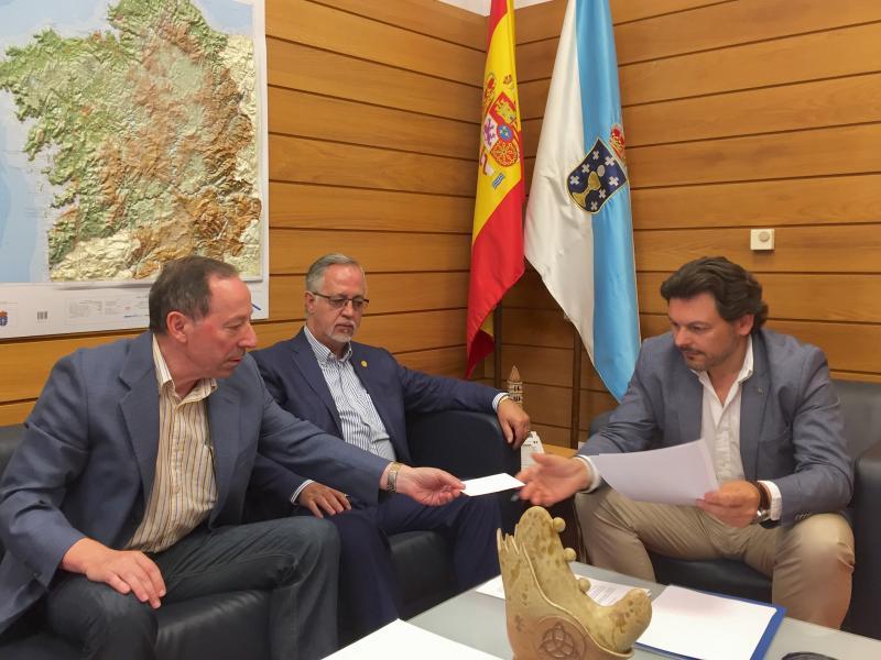 Miranda, Gulías (ámbolos dous ao carón das bandeiras) e Manuel Prado, durante a reunión mantida no despacho do secretario xeral da Emigración en Santiago de Compostela