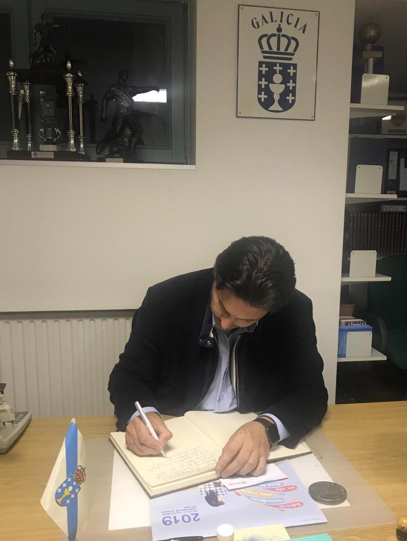O secretario xeral da Emigración, asinando no Libro de honra do Centro Galego de Hannover